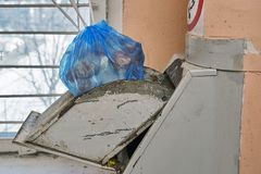 Garbage bag full of a garbage lying in a lid of a home garbage chute. In Moscow dwelling house Stock Photos