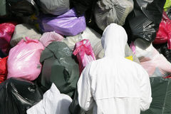 Garbage Bags. Many Garbage Plastic Bags, Back Of Man In Protective Suit royalty free stock photos