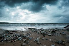 Garbage on beach, environmental pollution in Bali Indonesia. Storm is coming. And drops of water are on camera lens. Garbage on beach, environmental pollution in royalty free stock images