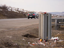 Garbage bin near the road. A garbage bin with garbage around in a dirty parking lot near the road Stock Photo
