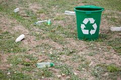 Garbage bin next to plastic trash on a ground background. Bright container for rubbish recycling. Environment, ecology Stock Image