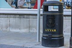 Garbage bin in a sidewalk of street stock photo