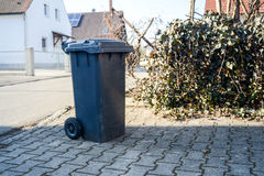Garbage bin stands at the curb Stock Photos
