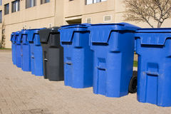 Garbage bins. Row of blue garbage bins with one black bin beside an apartment building Stock Photo
