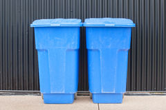 Garbage Bins. Blue garbage bins in front of brown metal siding Stock Photography