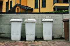 Garbage bins. Line of four garbage bins against a concrete wall in a residential area housing Royalty Free Stock Photos