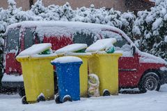 Garbage bins standing at the curbside. Garbage bins for recyclable materials and waste paper stand at the curbside during snowfall waiting for collection Stock Photos