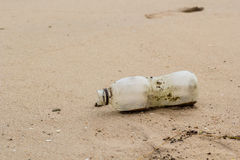 Garbage bottle on the beach Stock Photography