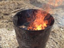 A metal barrel with lit trash burning with a bright flame royalty free stock photo