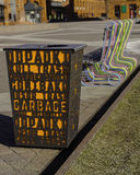 Garbage can. And colourful bench on the pavemant . Garbage with subtitles in different languages Royalty Free Stock Photos