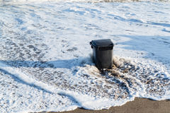 Garbage can in the tidal wave Royalty Free Stock Photos
