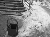 Garbage can and uncleaned stairs in the snow royalty free stock photo