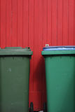 Garbage cans. Two green garbage or recycle cans sitting in front of a red wooden fence Royalty Free Stock Photography
