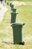 Garbage cans in the grass beside the road Royalty Free Stock Photography