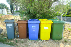 Garbage cans. NJIVICE, CROATIA - JUNE 24, 2017 : A group of garbage cans for recycling of waste lined up outside on the street in Njivice, Croatia Royalty Free Stock Photography