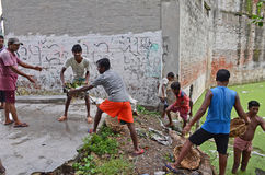 Garbage Cleaning. A group of municipality's labours work to clear waste and garbage from the trash-filled pond at slum area of Kolkata-India Royalty Free Stock Photo