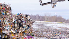 Garbage collecting machine disposed trash on the landfill. 4K stock footage