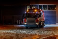 Garbage collecting truck leaves garage to collect garbage. Truck moves on snow covered road. Dark time of the day. Low key royalty free stock photography