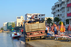 Garbage collection on the beach of Durres. DURRES, ALBANIA – August 31, 2015: Garbage collection on the beach of Durres. Albania has two faces - backwardness Stock Image