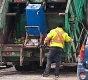 Garbage collector. A green garbage truck with a garbage collector wearing a yellow coat, trashing a blue garbages container in the compressor Royalty Free Stock Photo