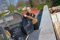 Garbage collector loading trash bag in truck. Garbage royalty free stock photo