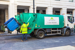 Garbage collector man loading trash bags on his truck. London, England - 10 April 2017 - Garbage collector operates his lift to load the trash from is container stock photography