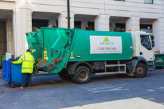 Garbage collector man loading trash bags on his truck. London, England - 10 April 2017 - Garbage collector operates his lift to load the trash from is container stock images