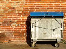 Garbage container. Locked garbage container beside red brick wall Royalty Free Stock Photography
