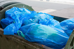 Garbage container filled with blue bags Royalty Free Stock Photo