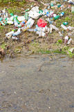 Garbage creek. Plastic bottles and other garbage thrown on to the shore of a small river Stock Photography