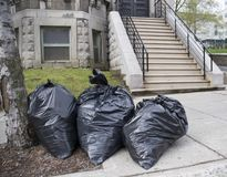 Garbage day. Bags of trash on sidewalk Royalty Free Stock Photos