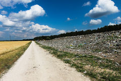 Garbage dump. Road between garbage dump and wheat field Royalty Free Stock Image
