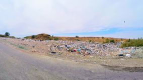 Garbage Dump Along Road In Ukraine. The shot was captured outside moving vehicle showing a spontaneous garbage scattered along the road side at city suburbs stock video footage