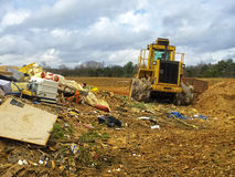 Garbage Dump Area. View of trash and heavy moving equipment at a dump site stock image