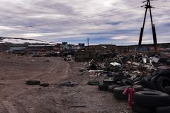 Garbage dump. Dirt road in the middle of a garbage dump, old car tires, against a stormy sky Royalty Free Stock Photo