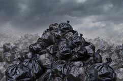 Garbage Dump. Garage dump concept with mountains of black waste bags of trash with an unpleasant smell  in an infinite landfill heap landscape as a background of Royalty Free Stock Photos