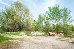 Garbage dump on the grass near the forest ecological disaster concept polluting nature and city park with litter and junk.  Royalty Free Stock Photography