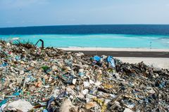 Garbage dump near the  beach close to ocean full of smoke, litter, plastic bottles,rubbish and trash at tropical island. Garbage dump near the  beach close to Royalty Free Stock Images
