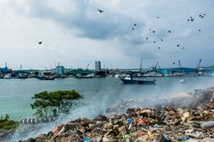 Garbage dump near harbor view full of smoke, litter, plastic bottles,rubbish and trash at the Thilafushi local tropical island Stock Photo