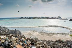 Garbage dump near the ocean full of smoke, litter, plastic bottles,rubbish and trash at the Thilafushi local tropical island. Garbage dump near the ocean full of Stock Images