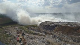 Garbage dump pollutes the environment. Strong wind rises toxic smoke of burning garbage into the air. Fire burning public dump is polluting a clean ecological stock footage