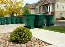 Garbage Dumpsters. Green garbage dumpsters waiting for curbside pick-up on trash day in residential neighborhood Royalty Free Stock Image