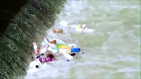 Garbage floating in the river. Garbage floating in the water of the river in the city. Pollution garbage dump. Dropping litter into rivers, industrial pollution stock video