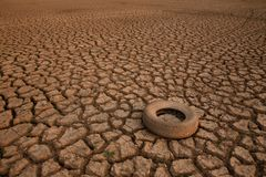 Water crisis and Climate change concept. Garbage of industry on cracked earth metaphor climate change, global warming environment pollution royalty free stock images
