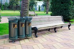 Garbage iron lattice bins for sorting garbage in a city park next to bench. Garbage iron lattice bins for sorting garbage in a city park next to a bench stock images