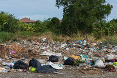Garbage and junk dump to the landfill. In field it illegal, hazardous and dangerous for environment Stock Photo