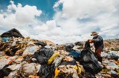 Garbage keeper. On big garbage heap under blue sky stock images