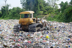 Garbage Landfill. Bulldozer spreads garbage in a landfill; rural area Royalty Free Stock Photography