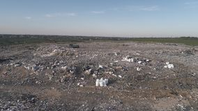Garbage on landfill, drone view on man running along city dump household waste and flying gulls over large rubbish piles stock footage