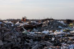 Garbage on the landfill and working bulldozer Stock Image